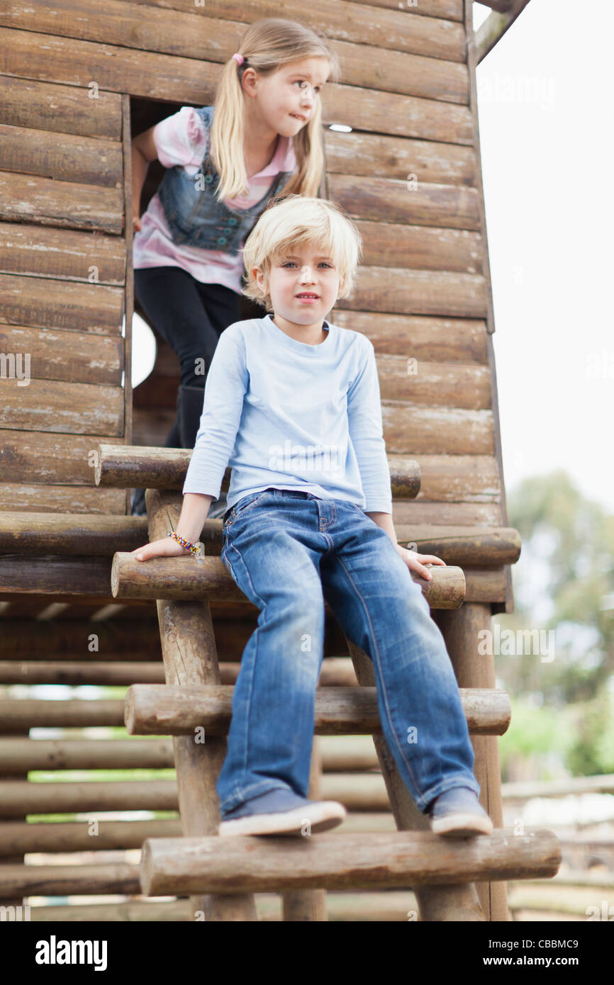 Children climbing out of playhouse - Stock Image