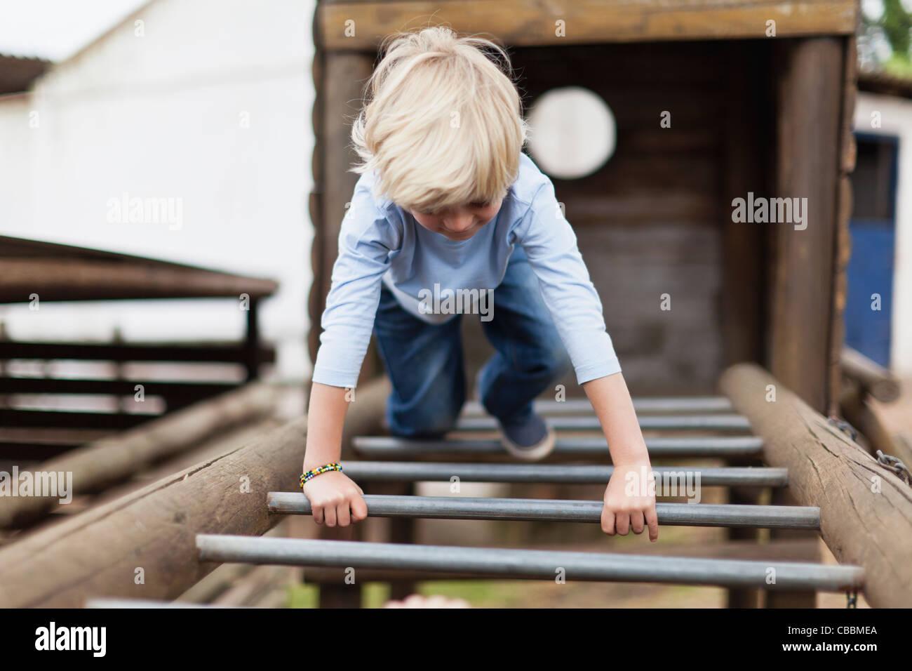 Boy playing on monkey bars - Stock Image