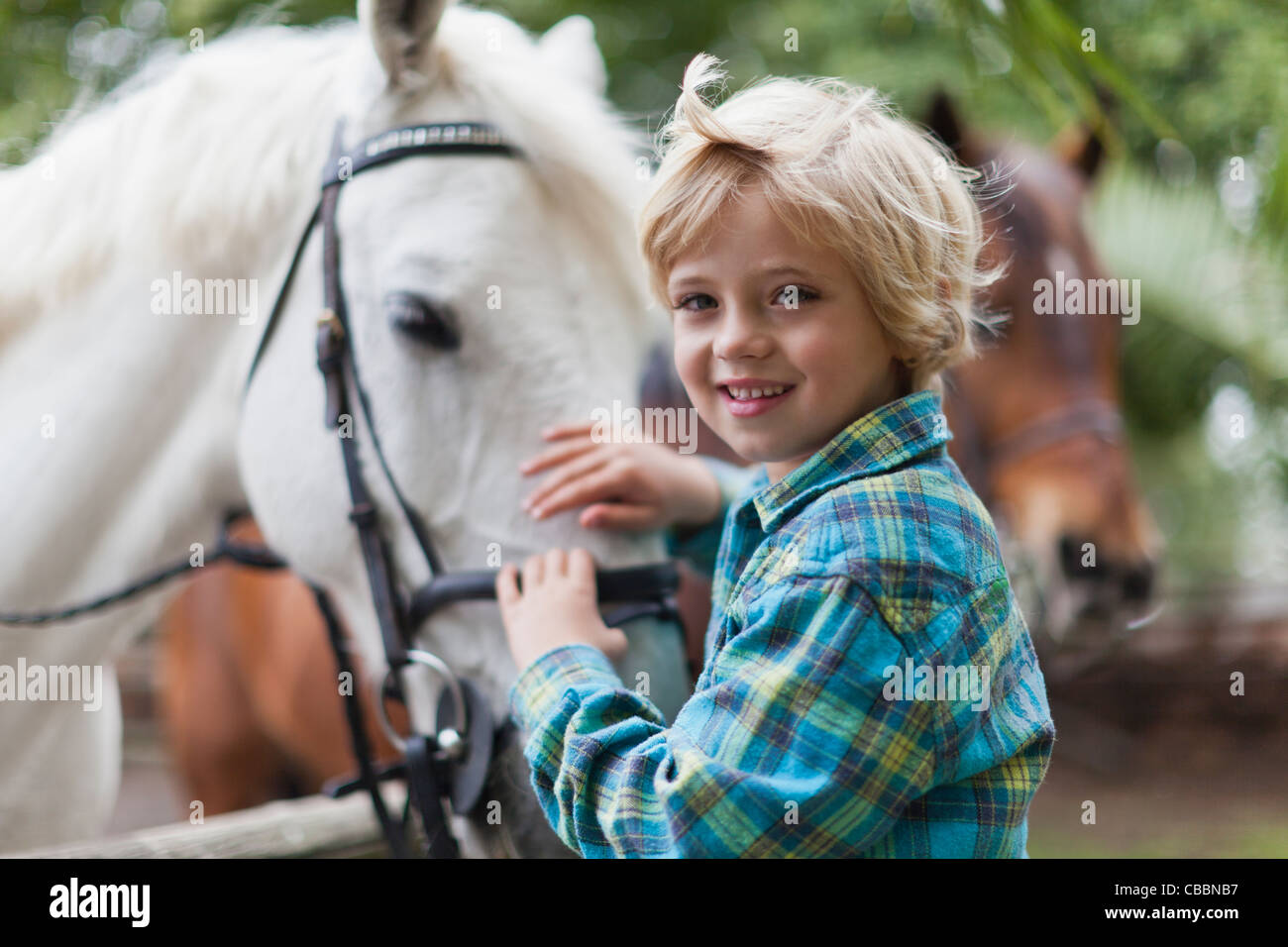 Smiling boy petting horse in yard - Stock Image