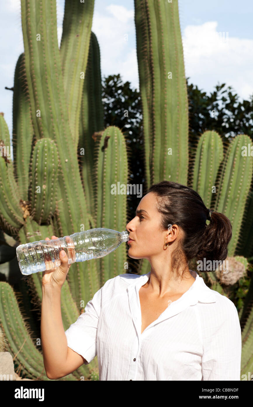 Woman drinking from water bottle in front of a cactus - Stock Image