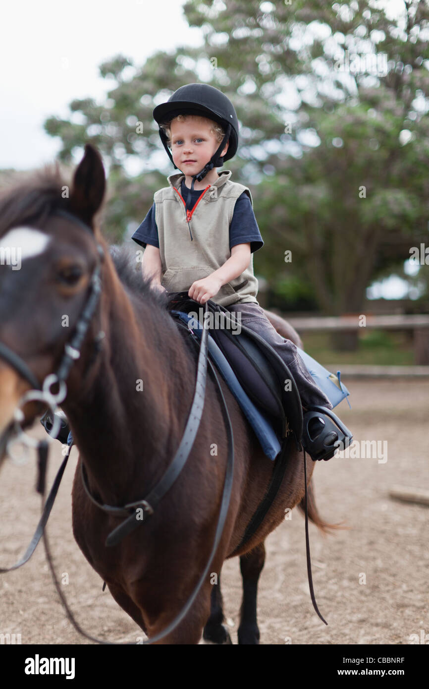 Boy riding horse in yard - Stock Image