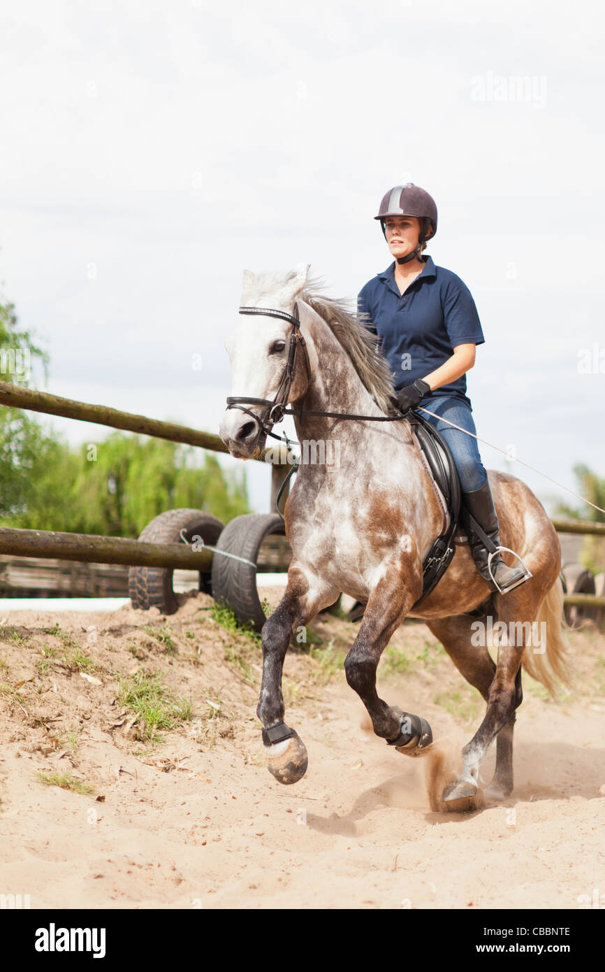 Woman riding horse in yard - Stock Image