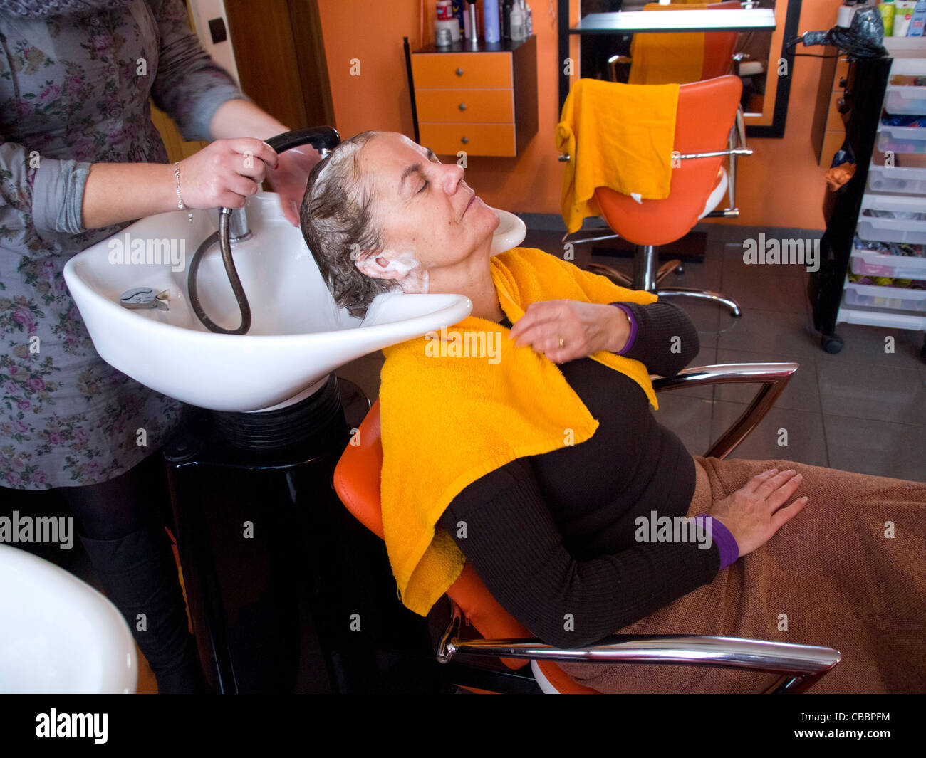 Middle-aged woman having her hair washed in the hair salon - Stock Image