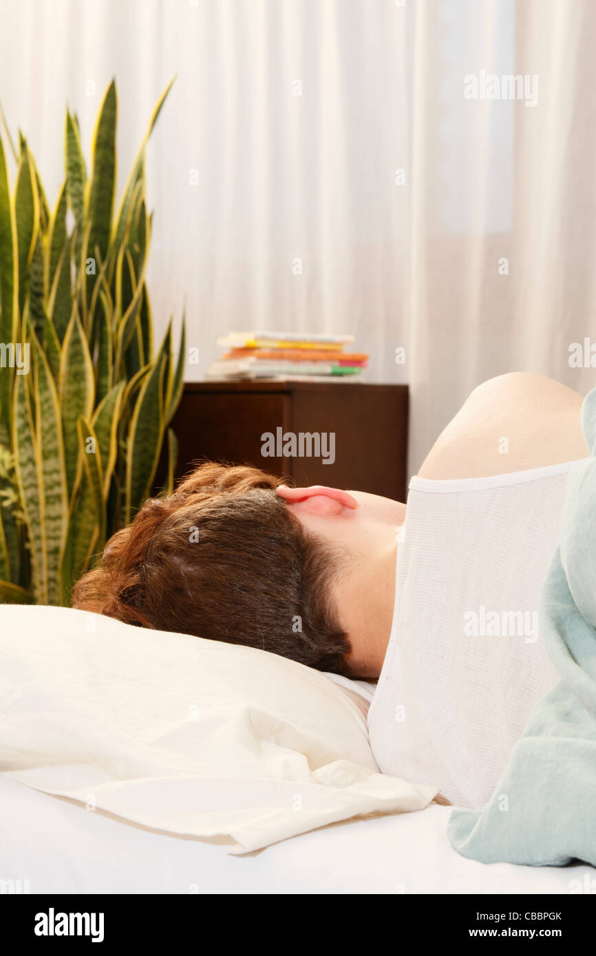 Man asleep in bed - Stock Image