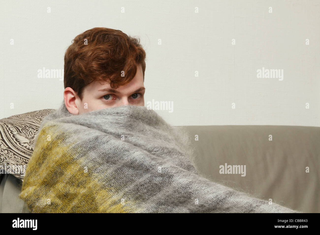 Man wrapped in blanket on couch - Stock Image