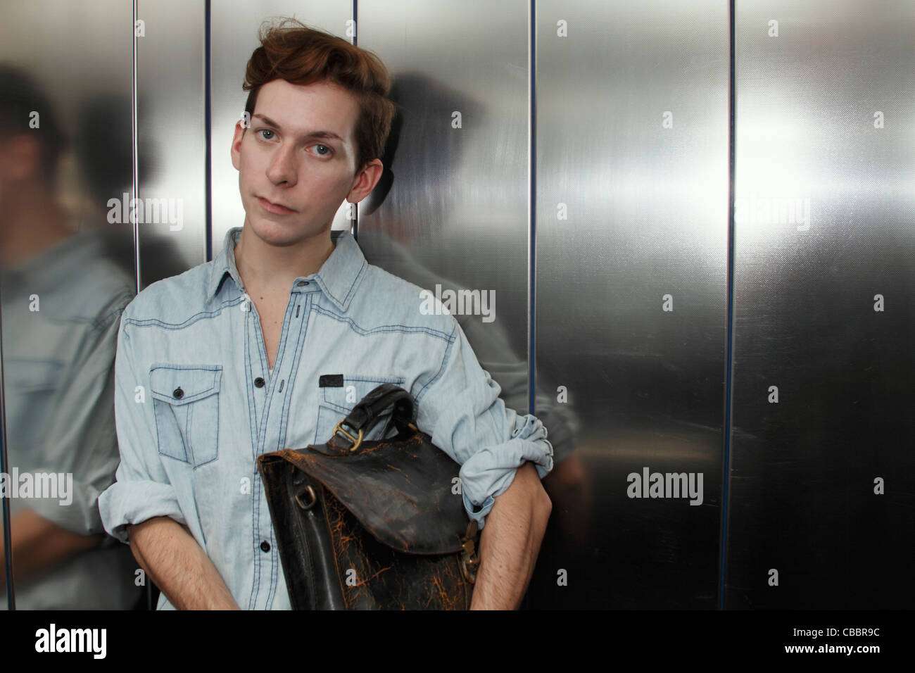 Man holding briefcase in elevator - Stock Image