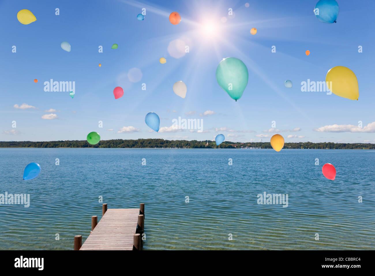 Balloons floating over still lake - Stock Image