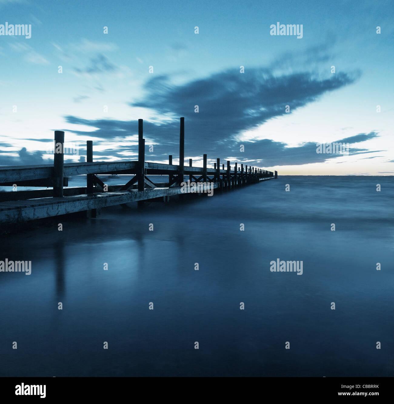 Wooden pier over ocean - Stock Image