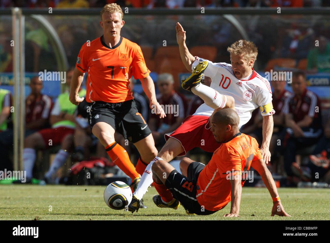 Nigel de Jong of the Netherlands tackles Martin Jorgensen of Denmark (10) during a 2010 FIFA World Cup match. Stock Photo