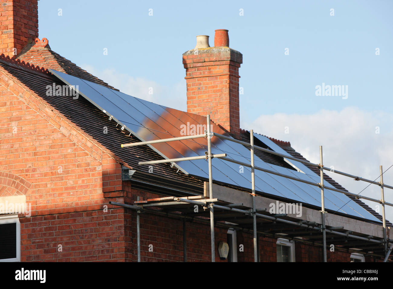 Newly installed solar panel array,to generate renewable energy from the sun. Installation is on a pitched roof on - Stock Image