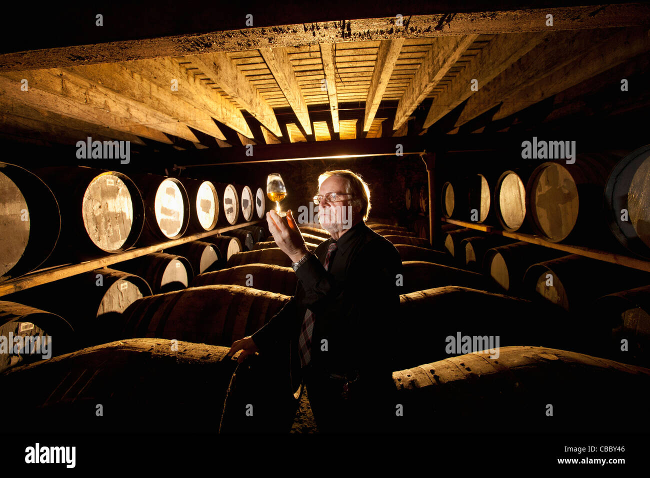 Worker testing whisky in distillery - Stock Image