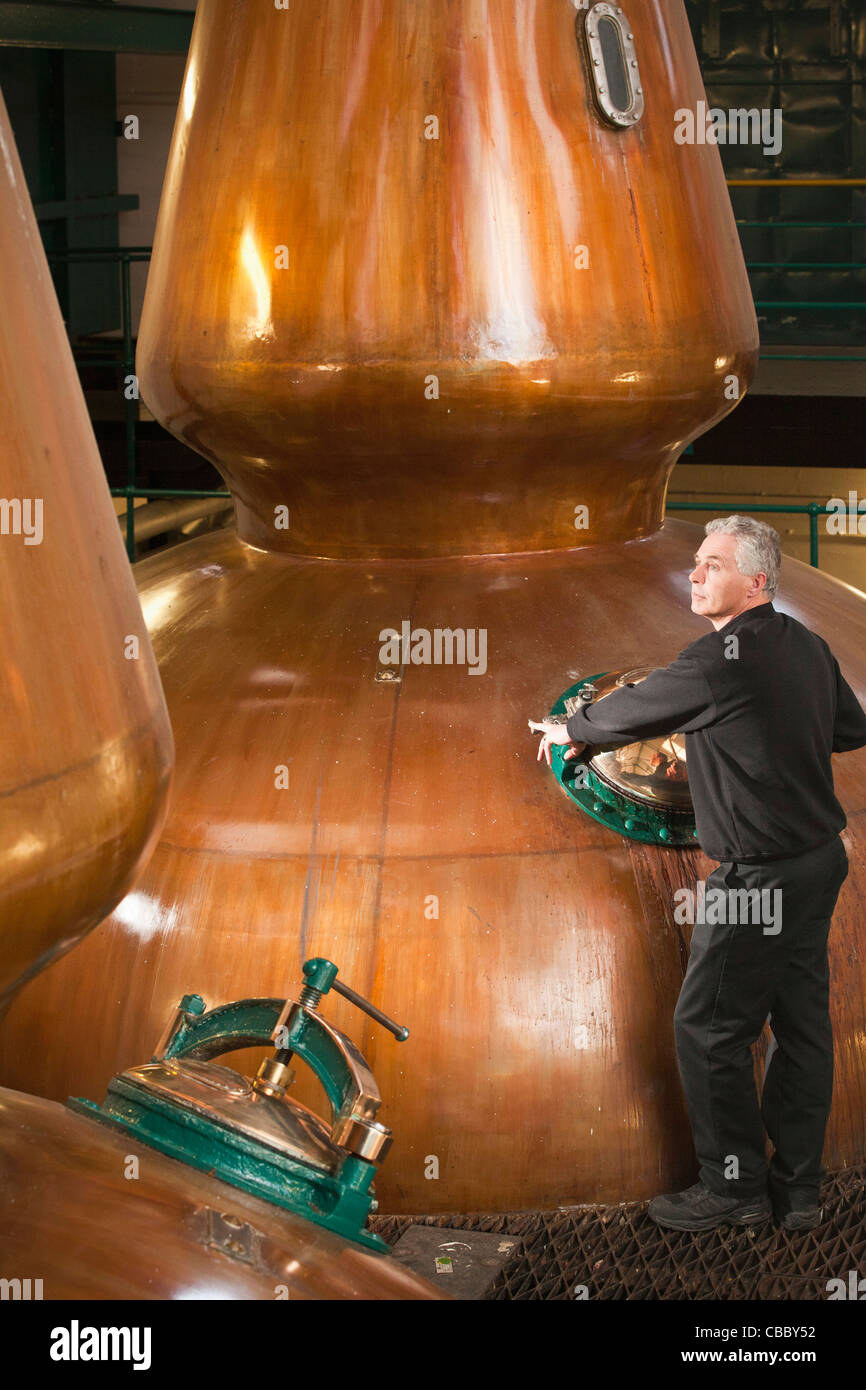 Worker in whisky distillery - Stock Image