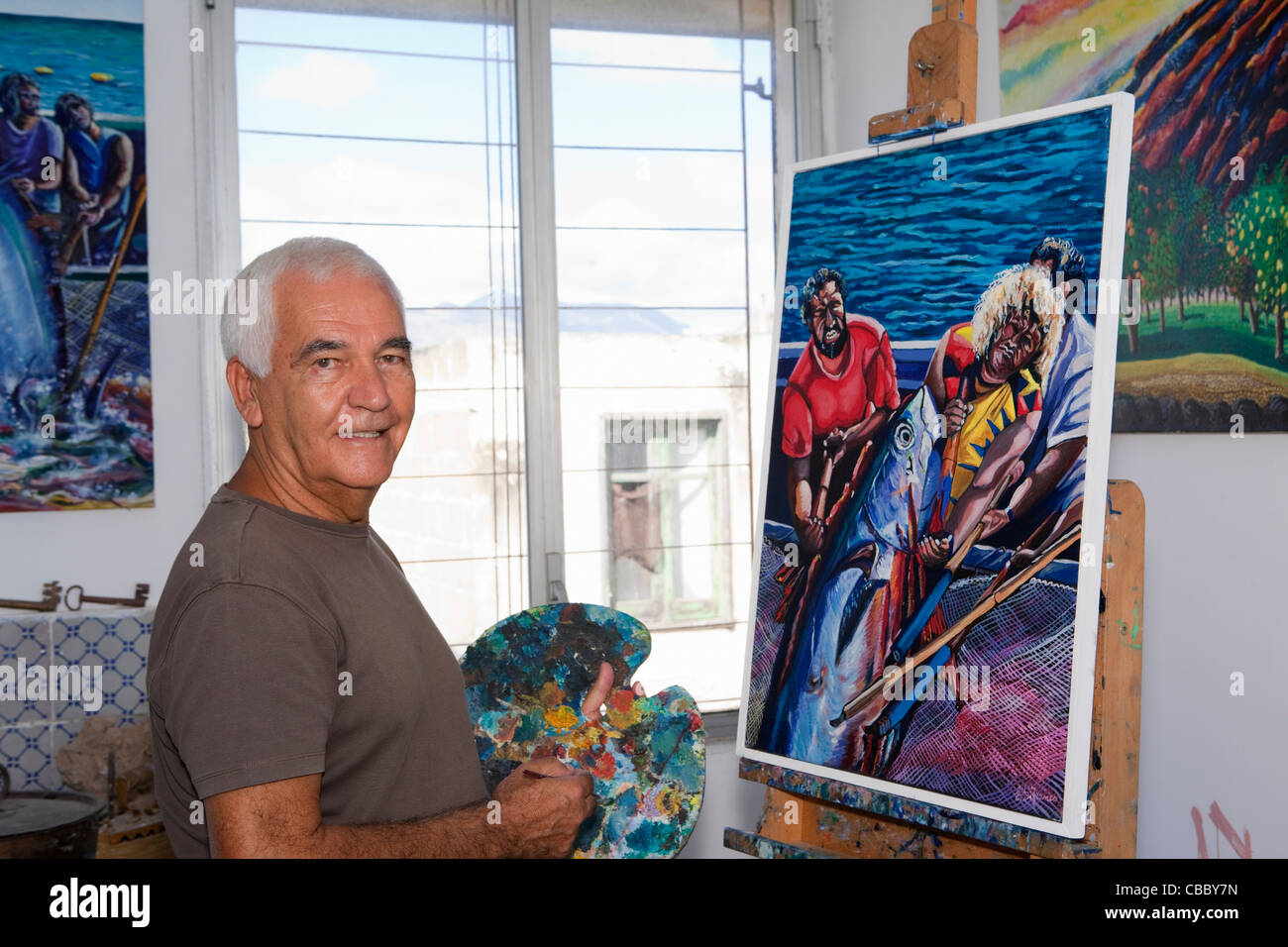Older artist painting in studio - Stock Image