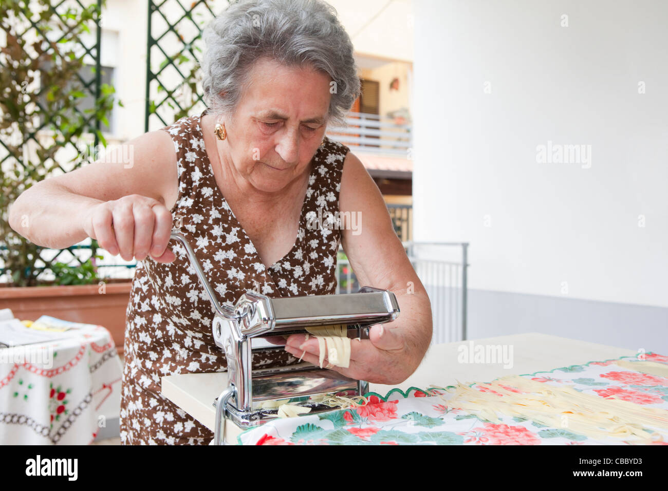 Older woman making pasta with roller - Stock Image