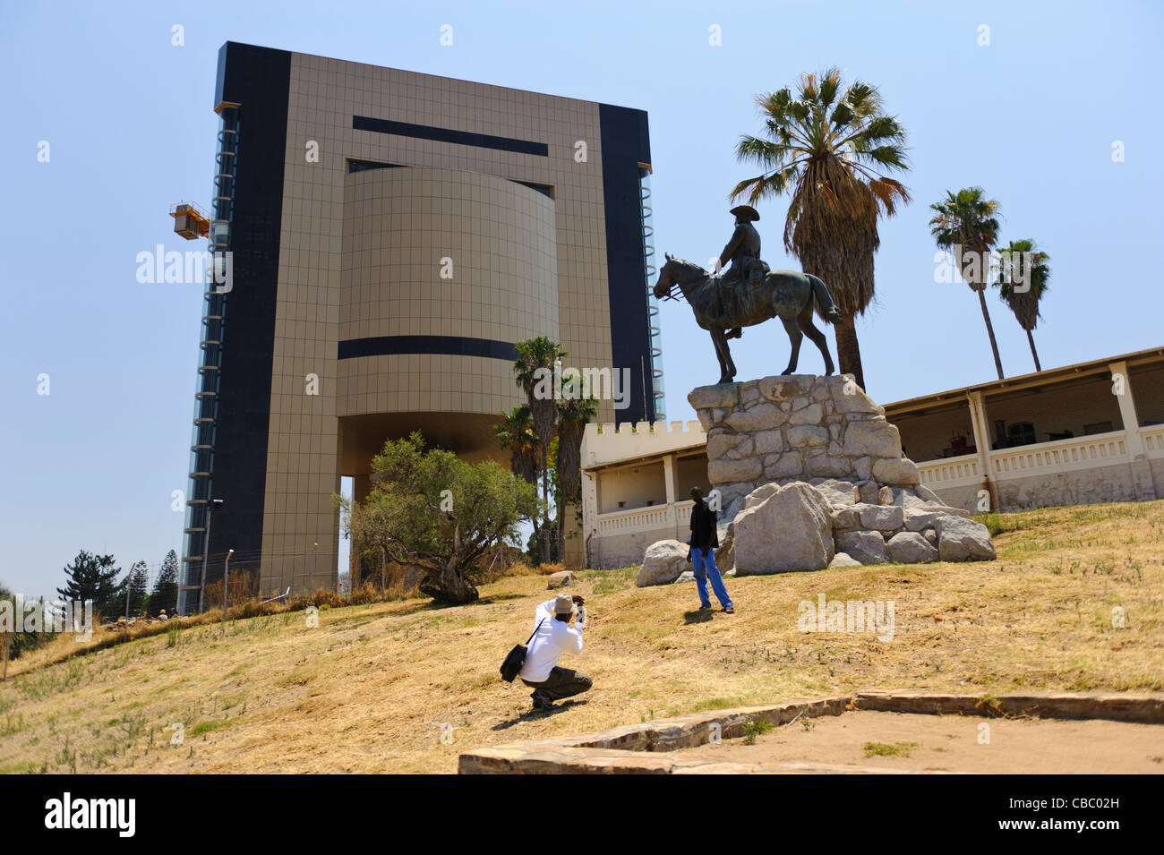 Disharmony in town-planning. A modern high rise building oppresses the historical relics in Windhoek, Namibia - Stock Image