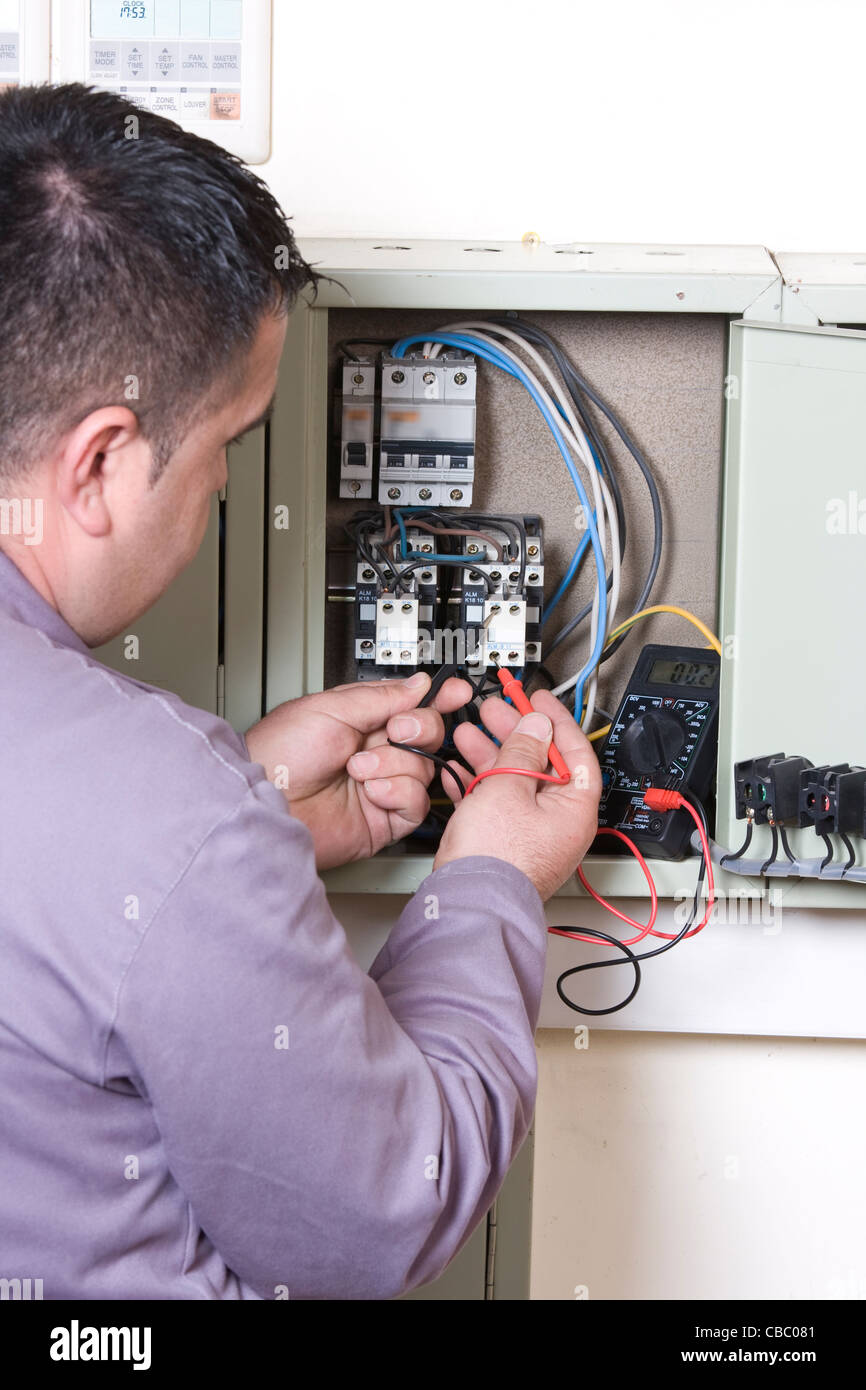 Electrician working on a panel - Stock Image