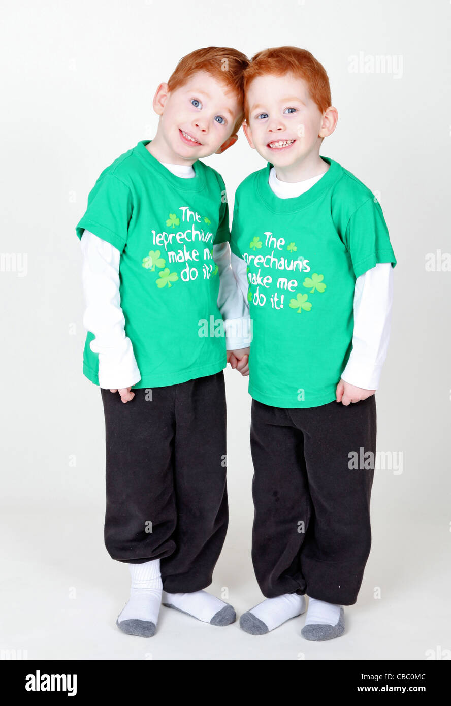 Smiling redheaded twins holding hands isolated on white - Stock Image