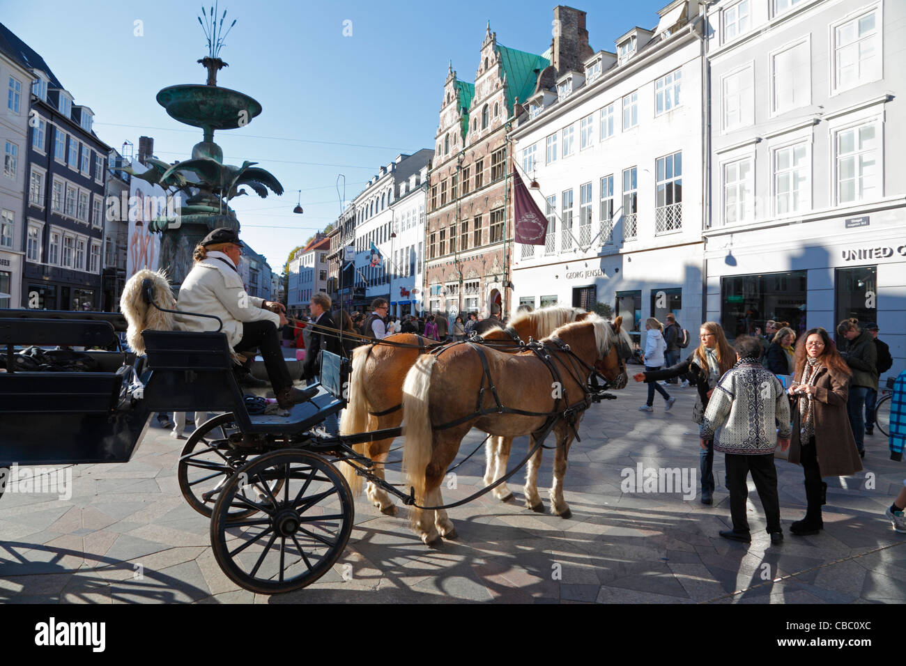 Horse-drawn cab waiting at the Stork Fountain on the pedestrian and shopping street Strøget in Copenhagen, - Stock Image