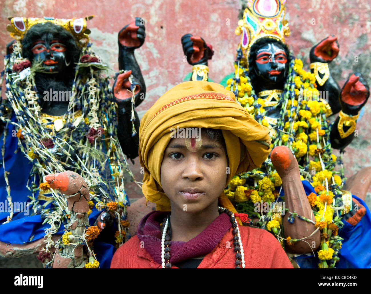 A young sadhu standing by sculptures of Hindu deities. - Stock Image