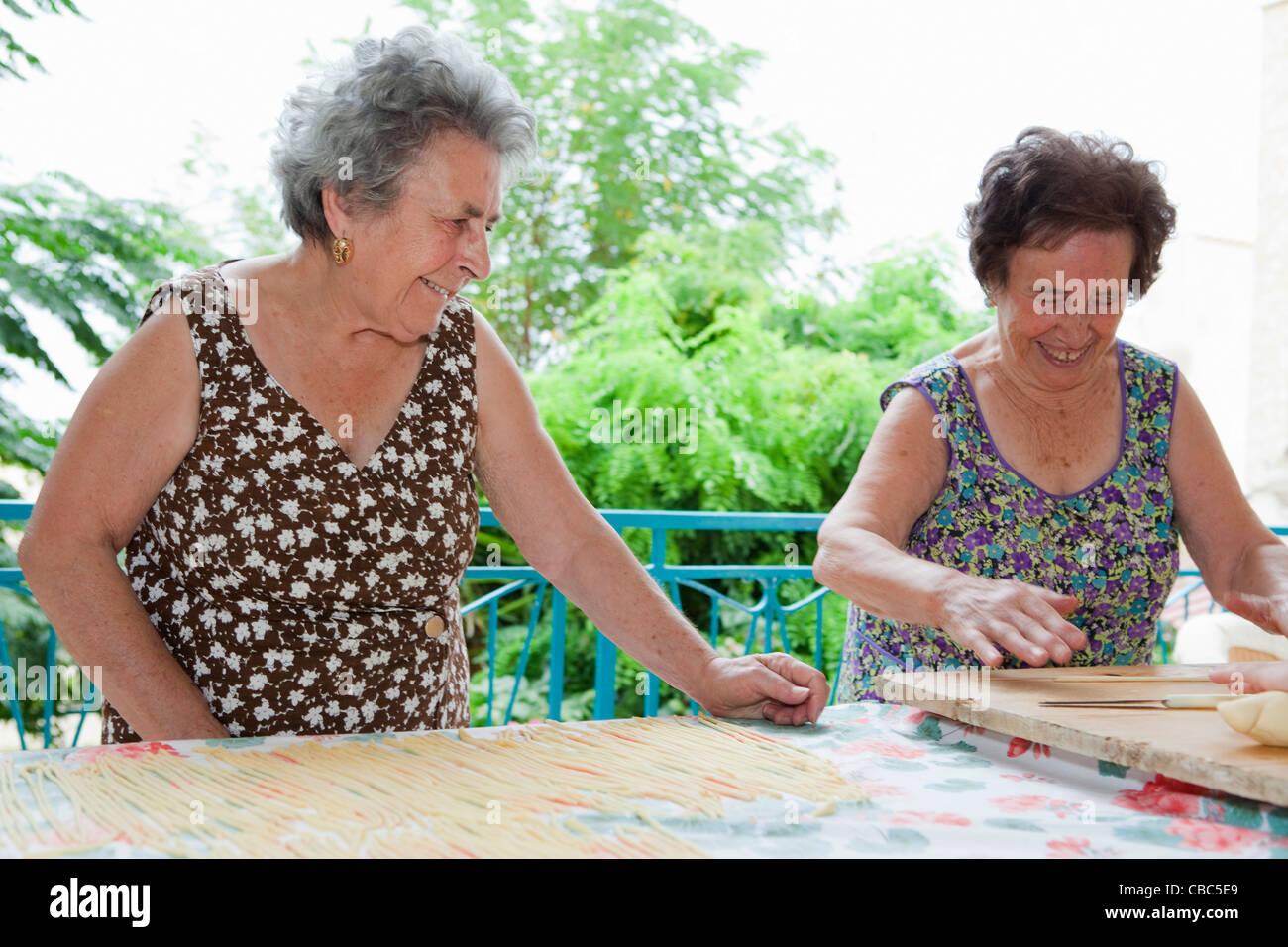Older women making pasta together - Stock Image