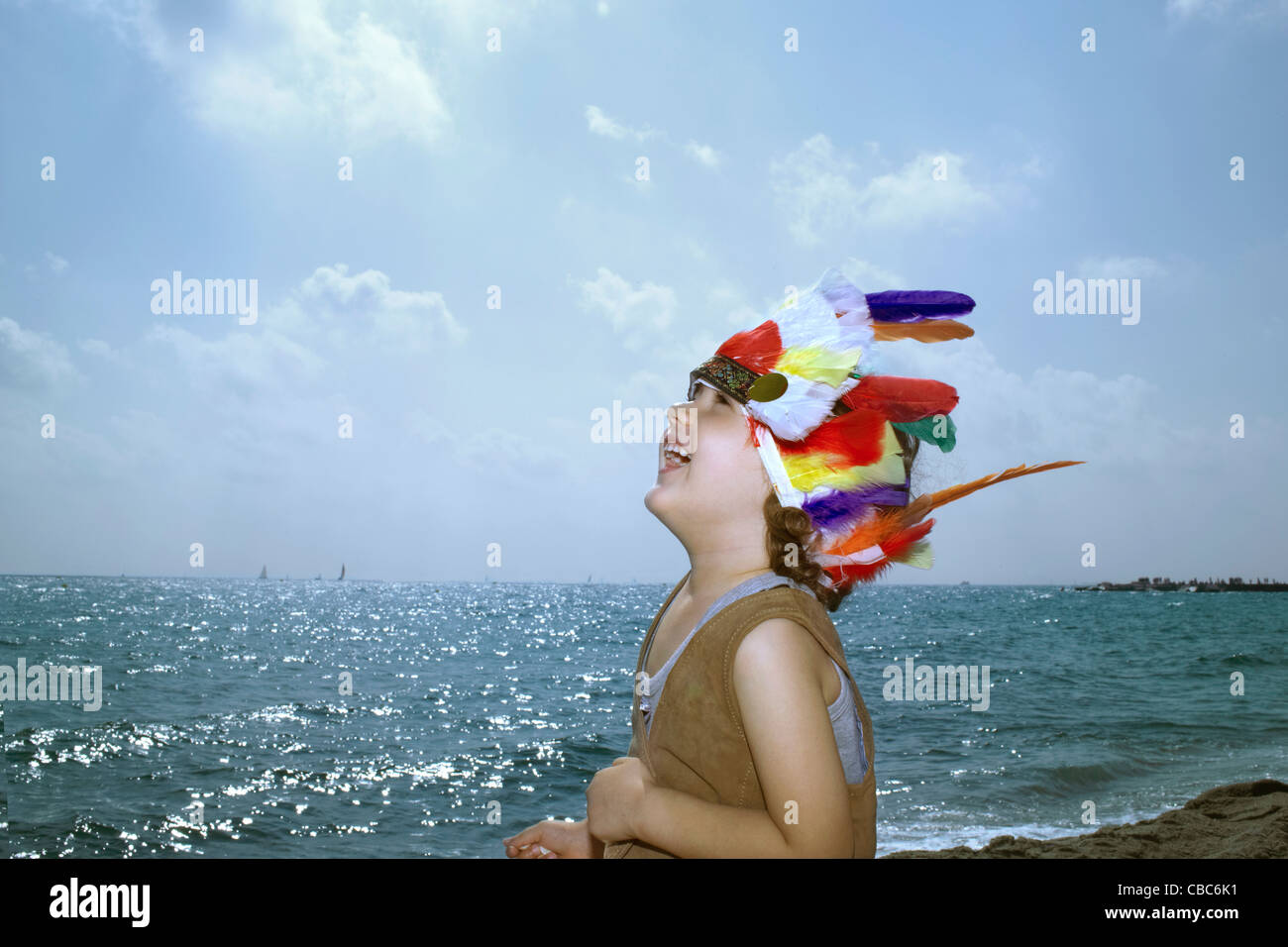 Toddler in Indian headdress on beach - Stock Image