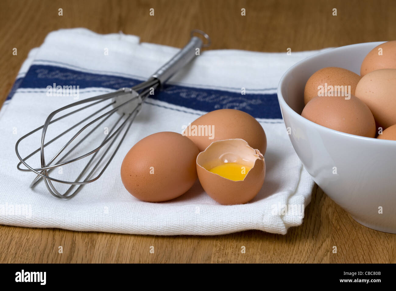 brown hens eggs on a white tea towel with a stainless steel whisk one egg cracked and separated showing egg white - Stock Image