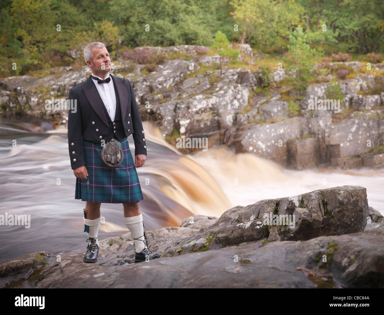 Time lapse view of man in kilt by river - Stock Image