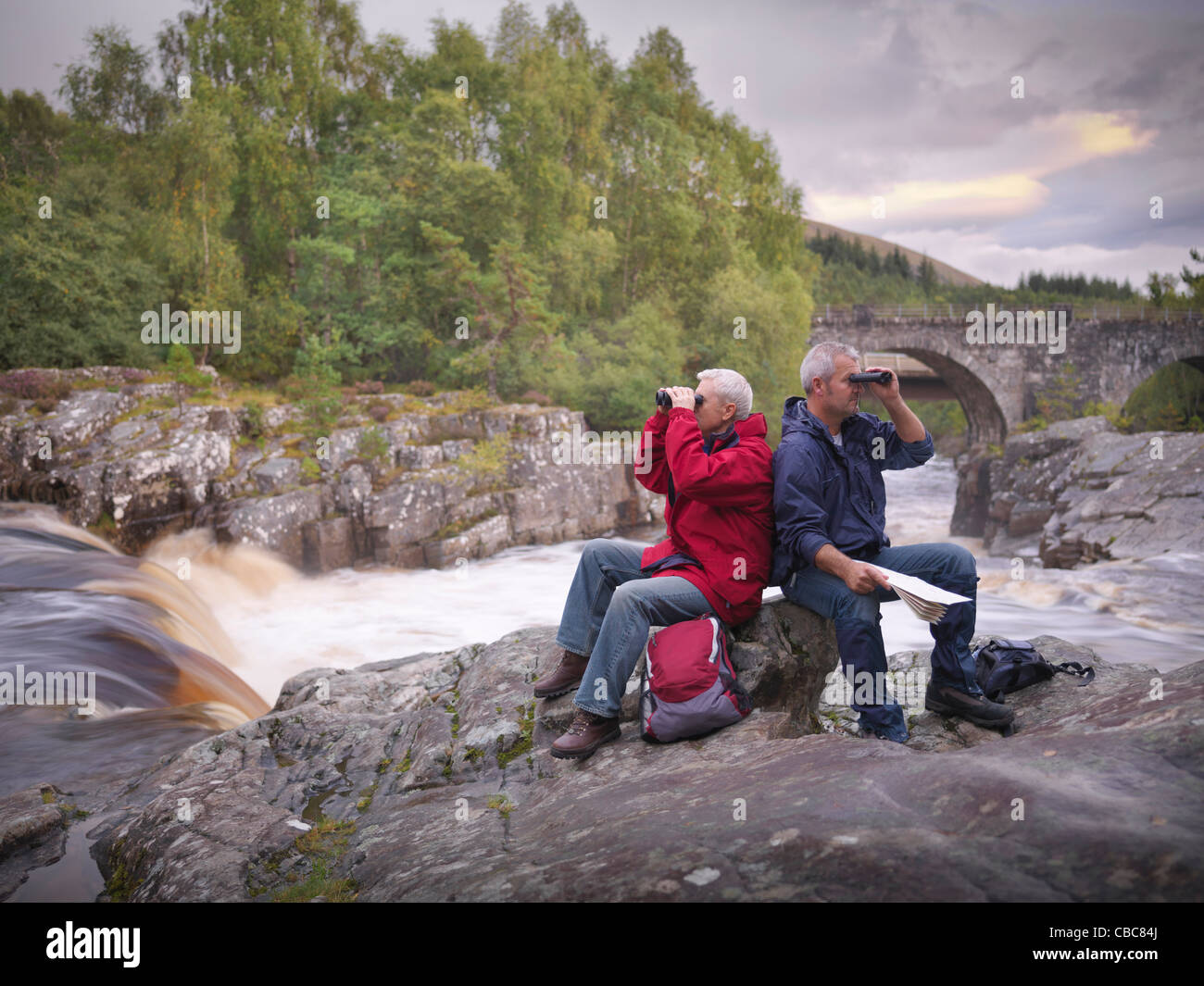 Hikers using binoculars by rocky river - Stock Image