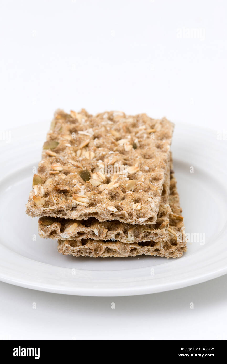 three ryveta crackers on a white plate isolated against a white background - Stock Image