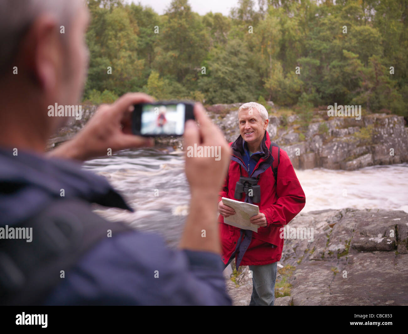Hiker taking picture of friend by river - Stock Image