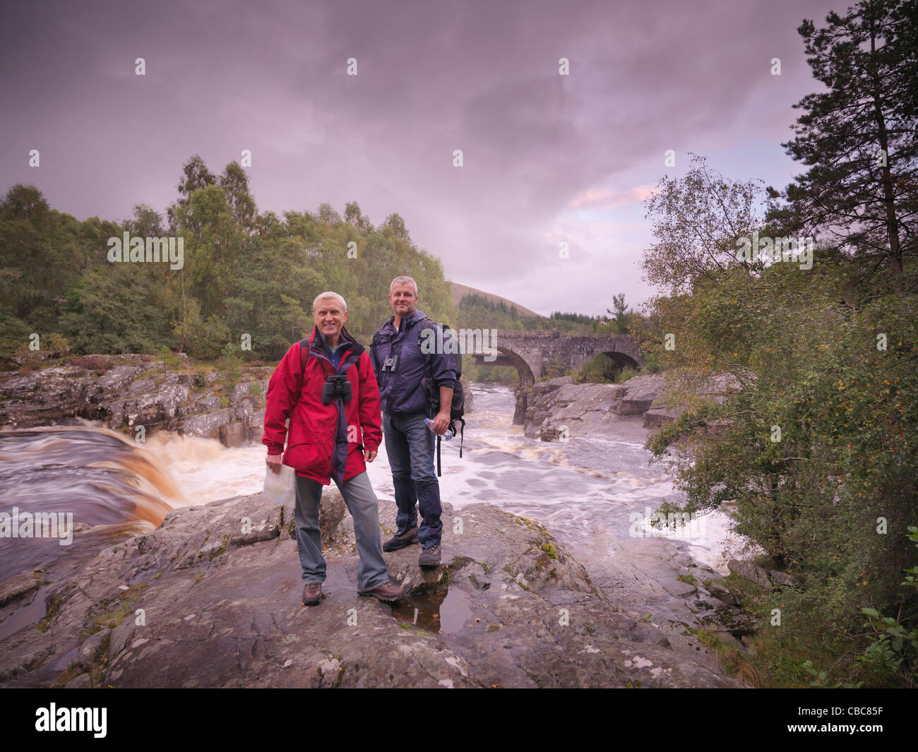 Hikers standing by rocky river - Stock Image