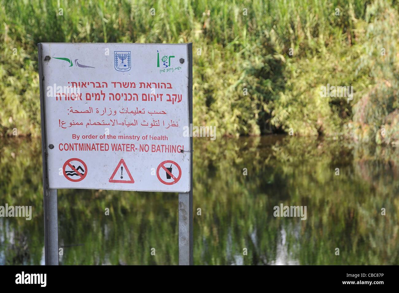 Israel, Hadera stream a seasonal watercourse nature reserve Contaminated water warning sign - Stock Image