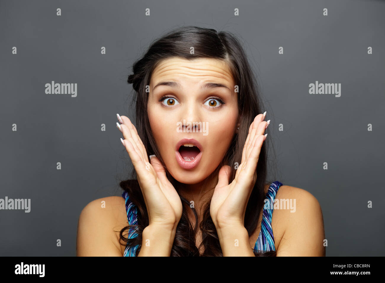 Portrait of astonished brunette looking at camera - Stock Image