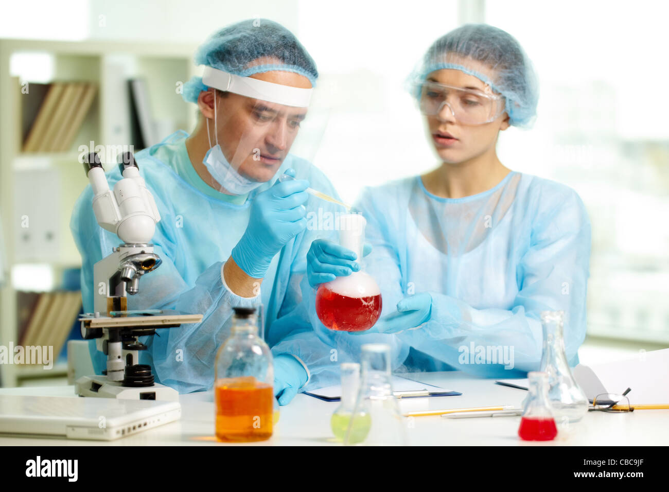 Laboratory worker is about to inject fluid into smoky chemical substance during experiment - Stock Image