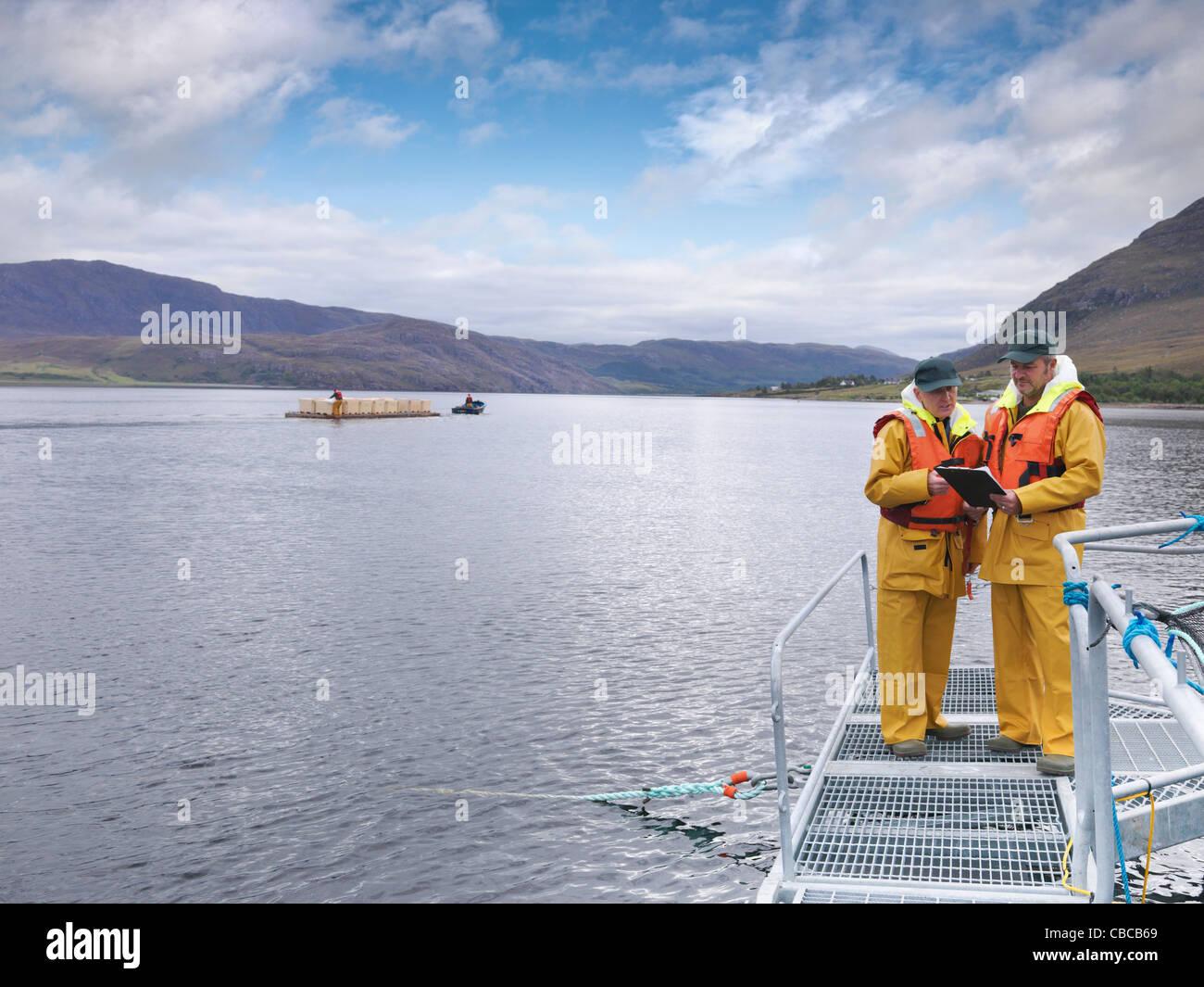 Fishermen talking on dock - Stock Image