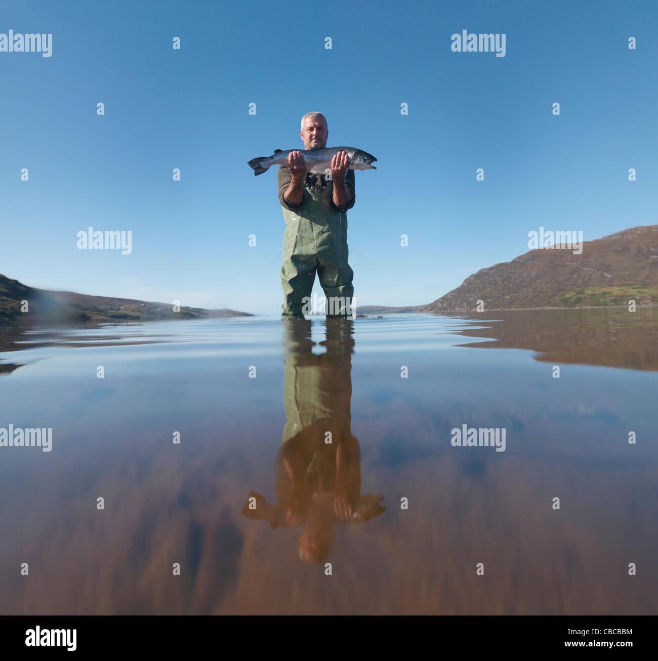 Fisherman with salmon in still lake - Stock Image