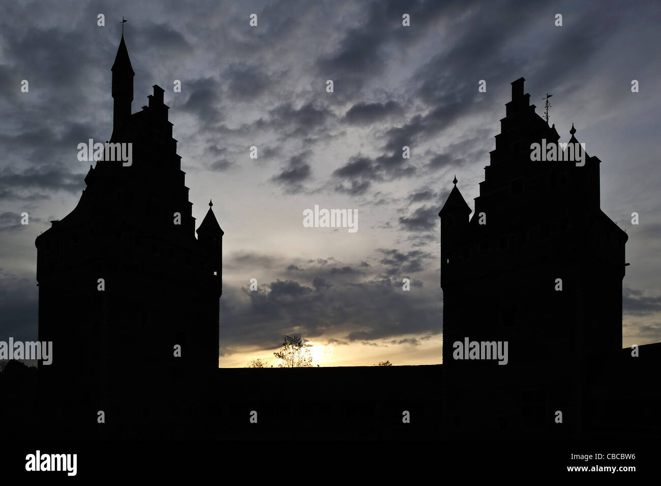 Creepy silhouetted step-roofed towers and turrets of the medieval Beersel Castle at sunset, Belgium - Stock Image