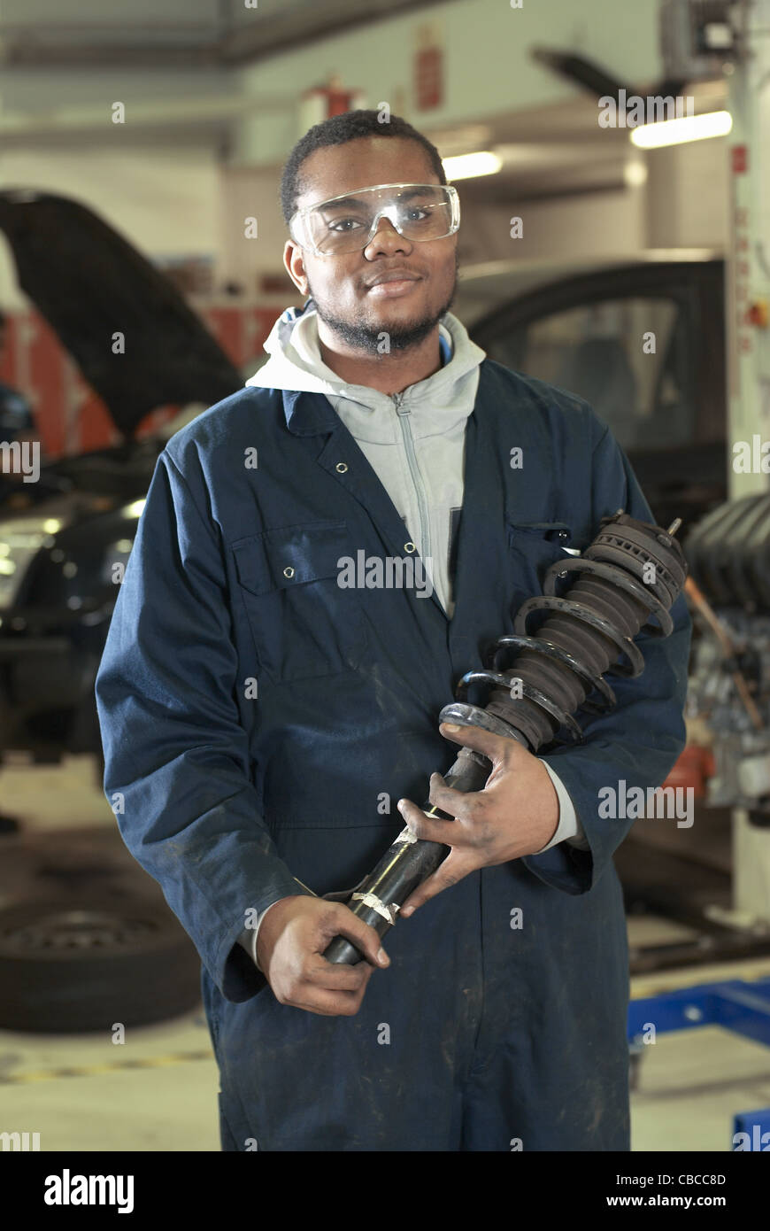Student carrying car part in garage - Stock Image