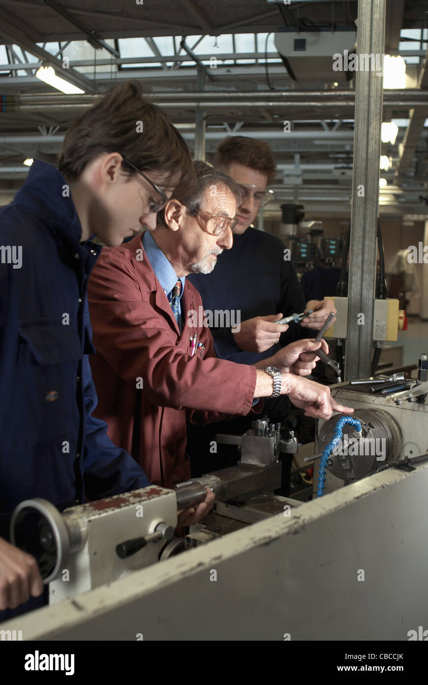 Teacher helping students in shop class Stock Photo