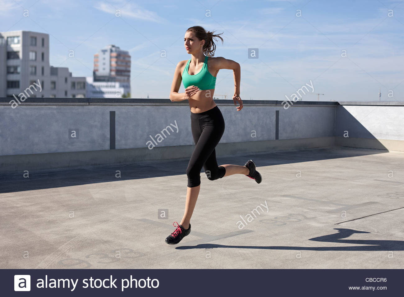 Woman jogging on rooftop - Stock Image