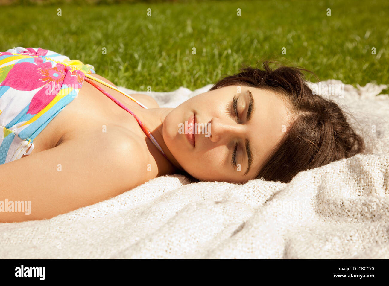 Woman sleeping on blanket in grass - Stock Image