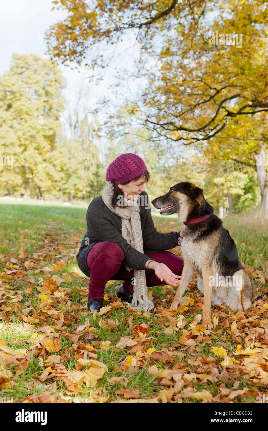 Smiling woman petting dog in park - Stock Image