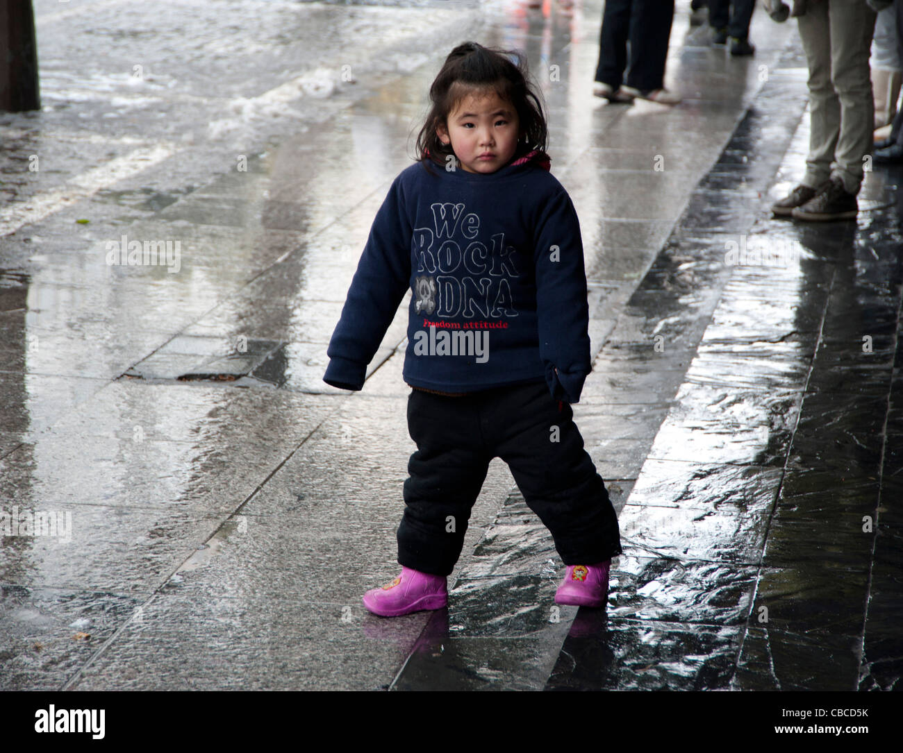 curious pre-schooler at wet street in Shanghai, China - Stock Image