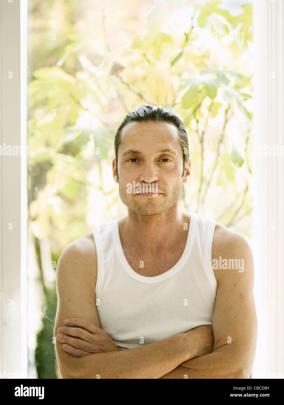 Man standing with arms crossed - Stock Image