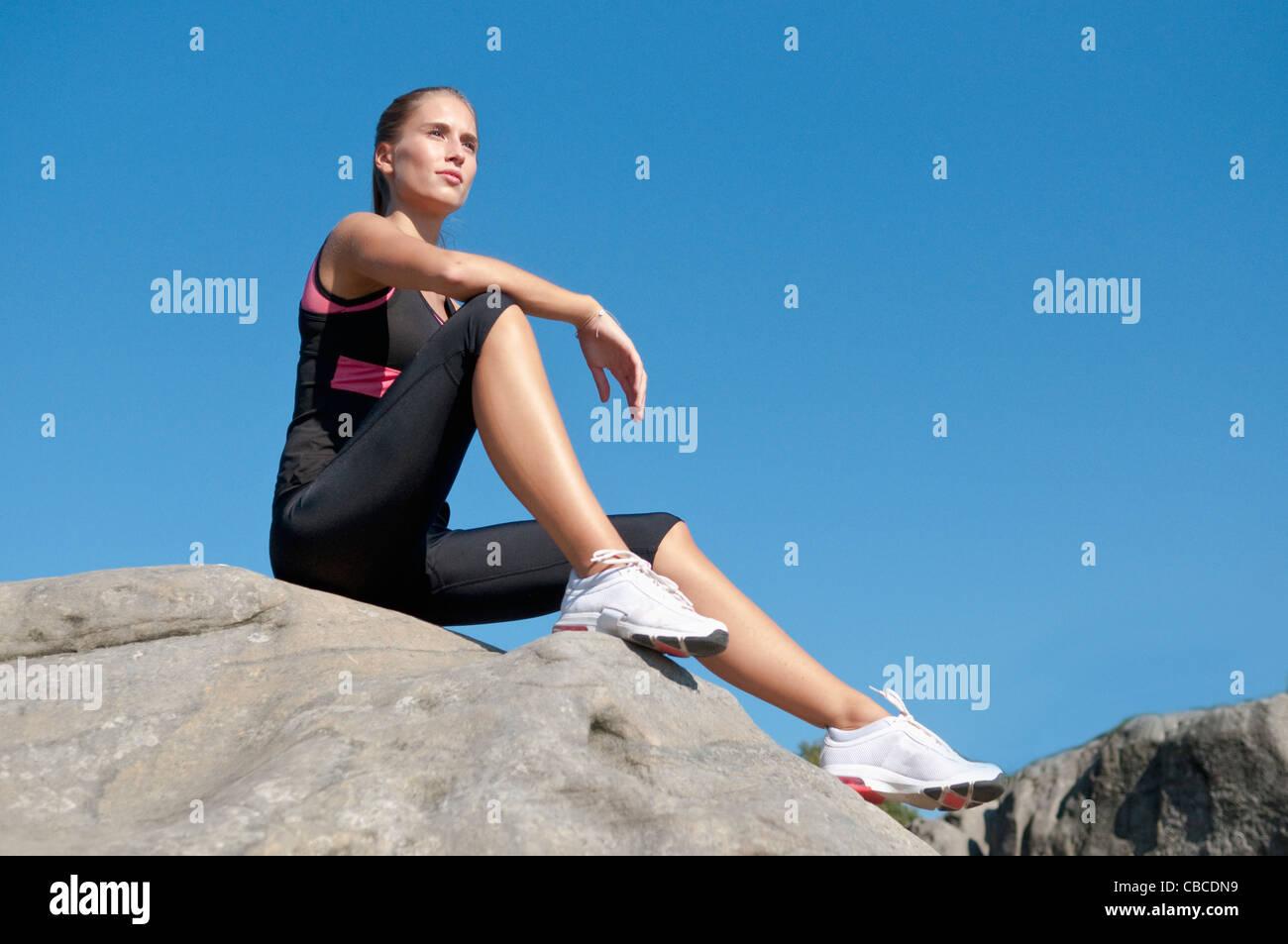 Rock climber resting on boulder - Stock Image