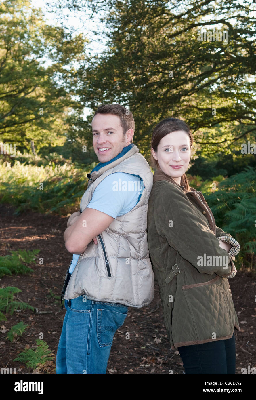 Couple standing back-to-back in park - Stock Image
