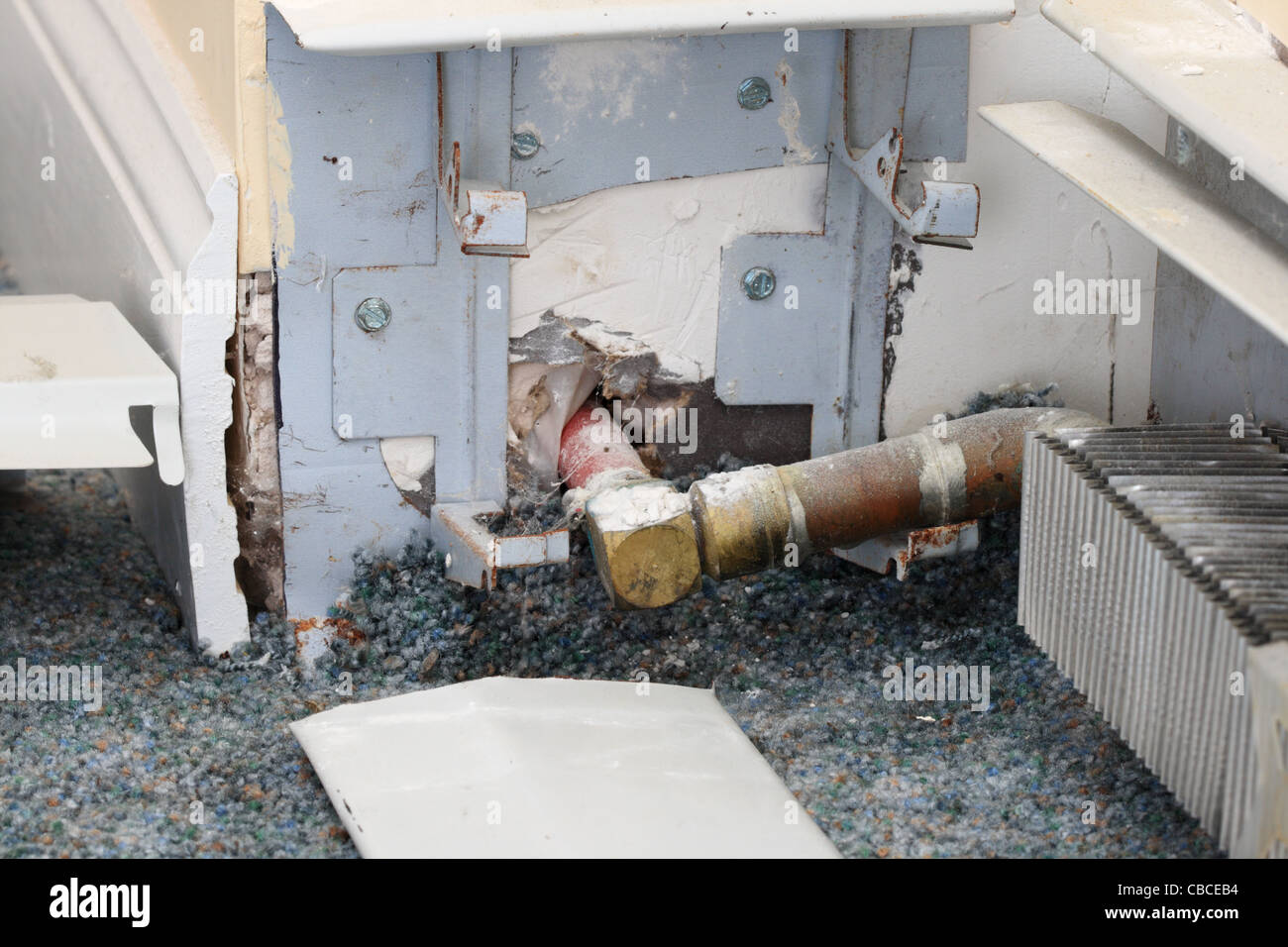 exposed baseboard heater heating pipe during home repair - Stock Image