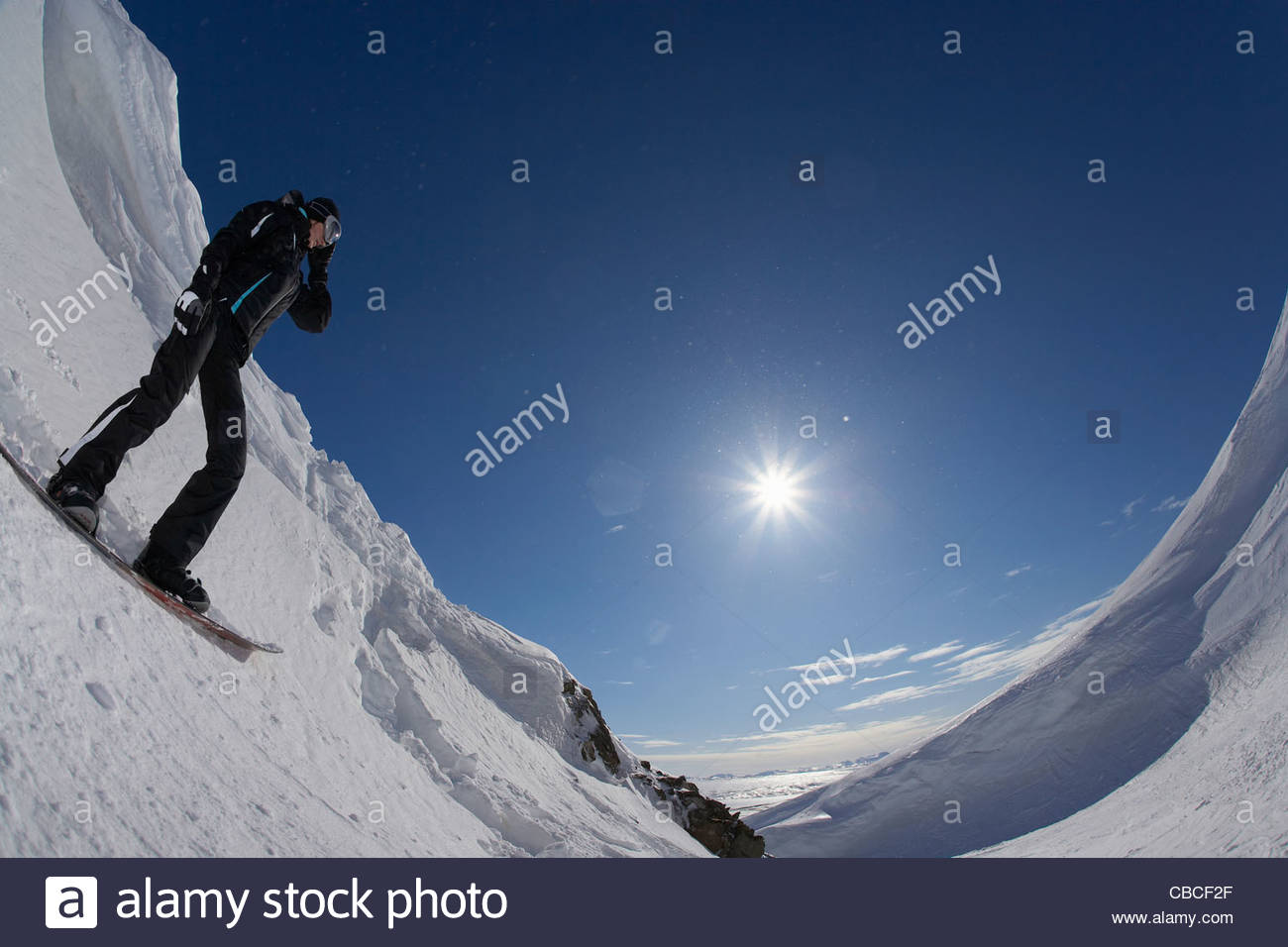 Snowboarder standing on slope - Stock Image