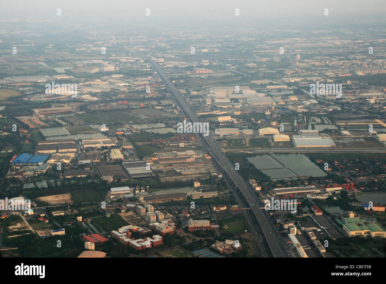 aerial image of the outskirts of Bangkok in Thailand with pollution haze - Stock Image