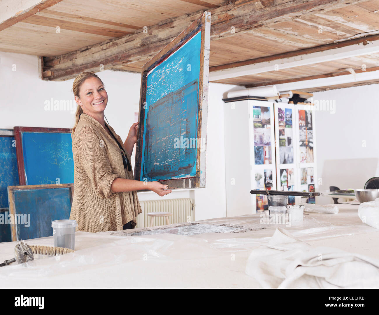 Designer with printing screen in studio - Stock Image